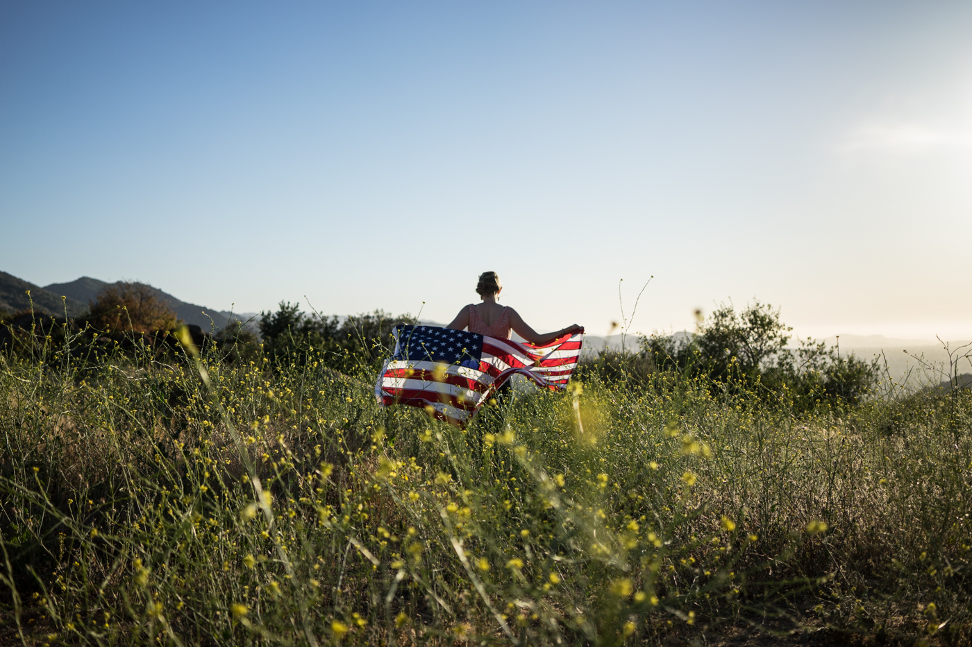 American woman with waving flag portrait in grassy wildflower meadow landscape at sunset