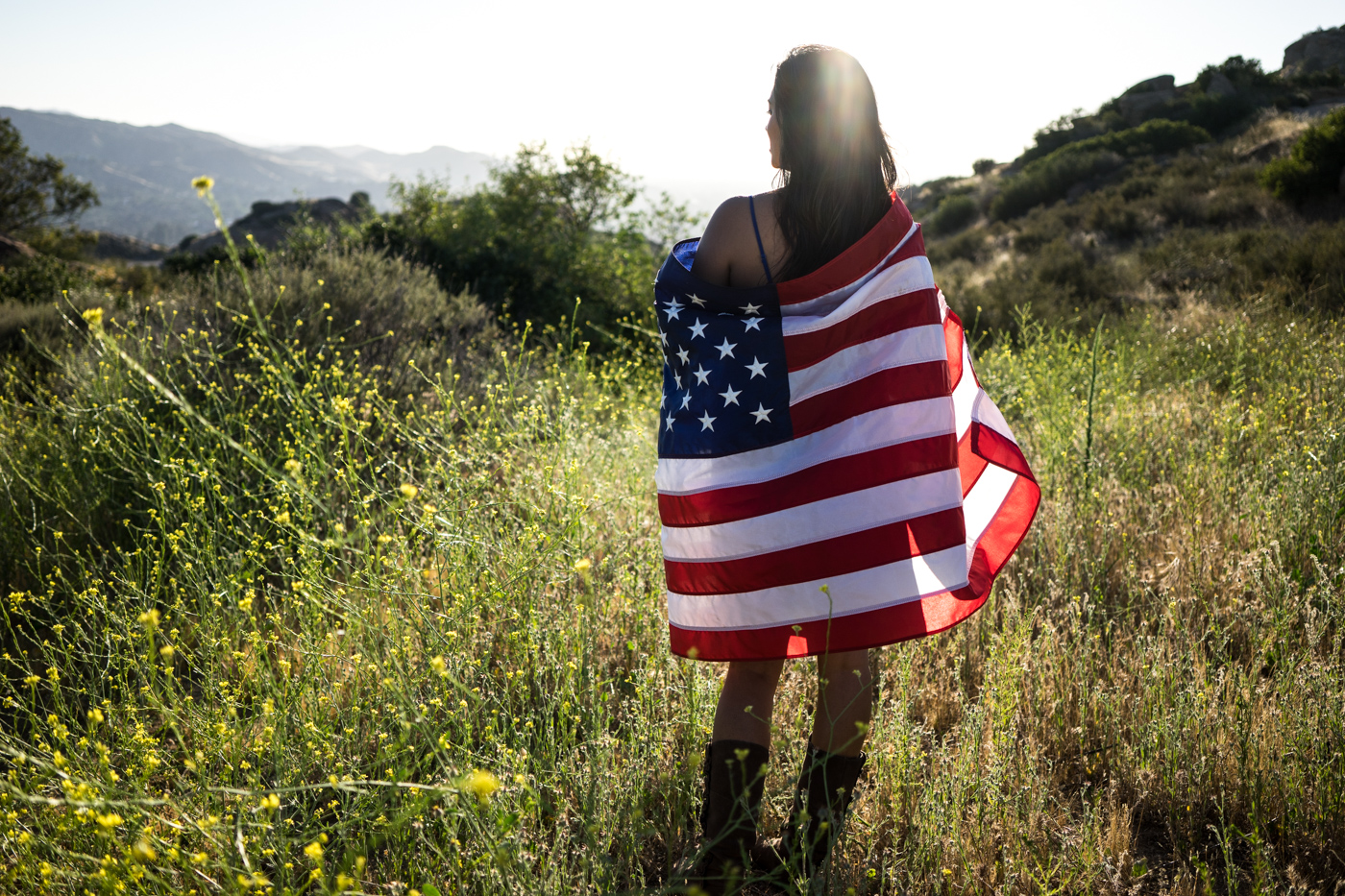 American woman with flag portrait in grassy mountain landscape at sunset
