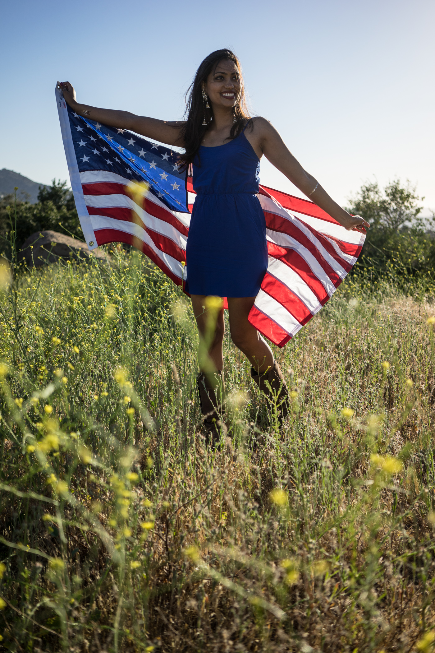 American woman with waving flag portrait in grassy mountain landscape at sunset