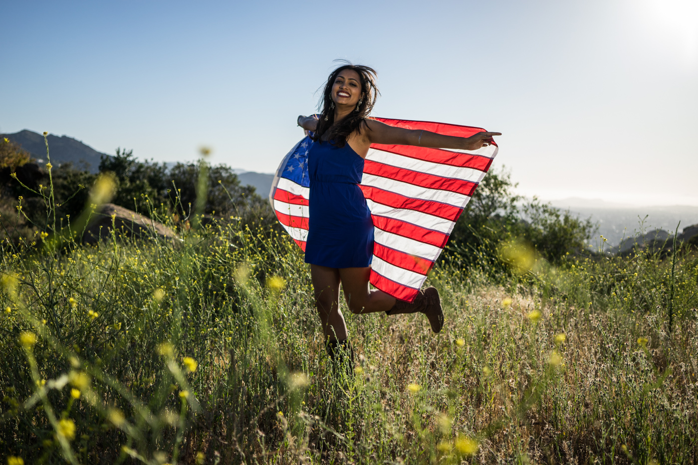 American woman jumping with flag portrait in grassy meadow landscape at sunset