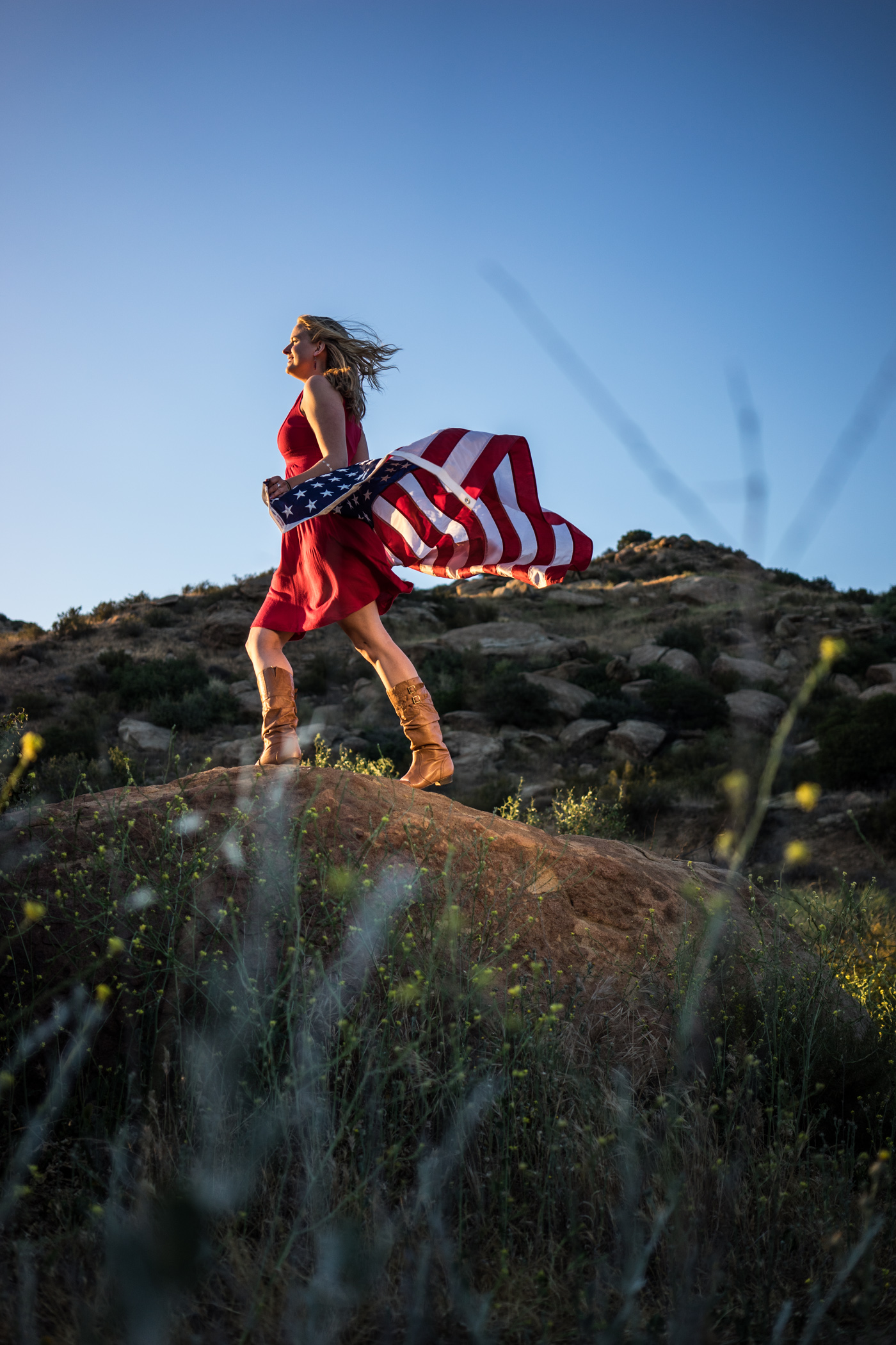 American woman and flag portrait in mountain landscape at sunset