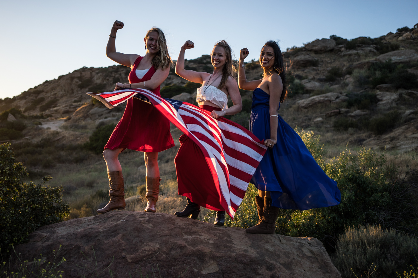 American women with waving flag portrait in grassy mountain landscape at sunset in rosy the riveter pose