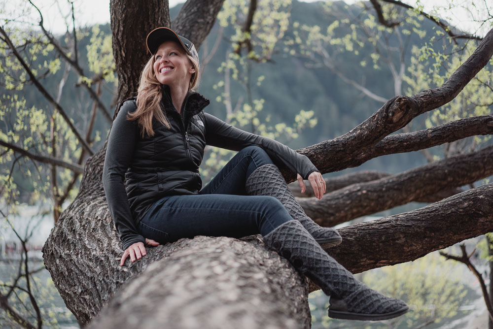 Cozy and Cute Camping Outfit on Stylish Travel Girl: Prana hat, North Face reversible vest, ICEWEAR top, GAP jeans, UGG Lattice Cardy boots